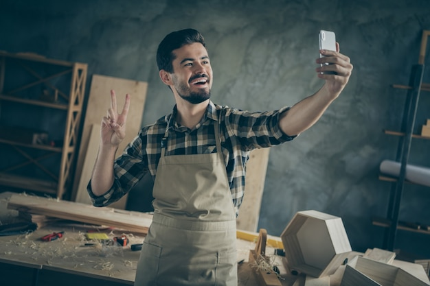 Positive success hardwood furniture restoration entrepreneur workman make selfie on smartphone show v-sign enjoy his workplace in home house garage