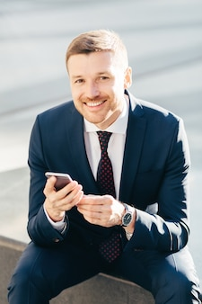 Positive successful male ceo sits outdoor, uses modern smart phone