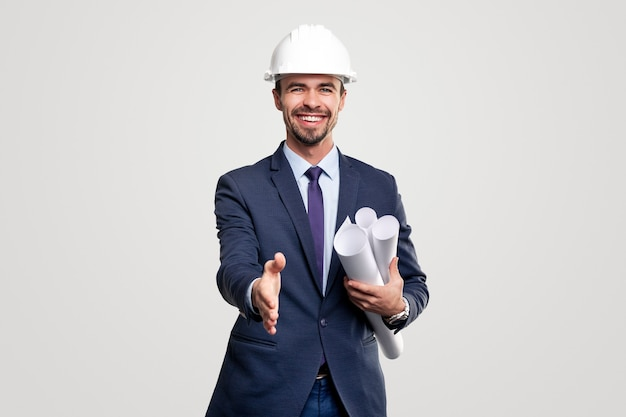 Positive successful male construction engineer in formal suit and hardhat with rolled blueprints outstretching hand for handshake to camera