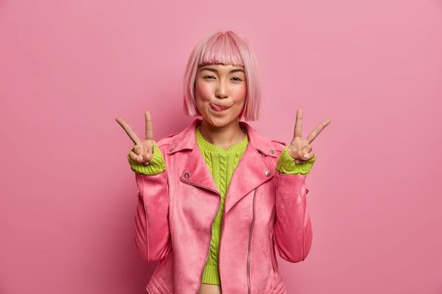 Позитивная успешная розоволосая азиатка облизывает губы, делает победный жест, показывает два пальца, одета в стильный пиджак, позирует в помещении