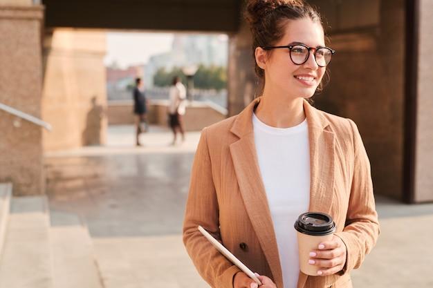 Позитивная успешная женщина гуляет по городу