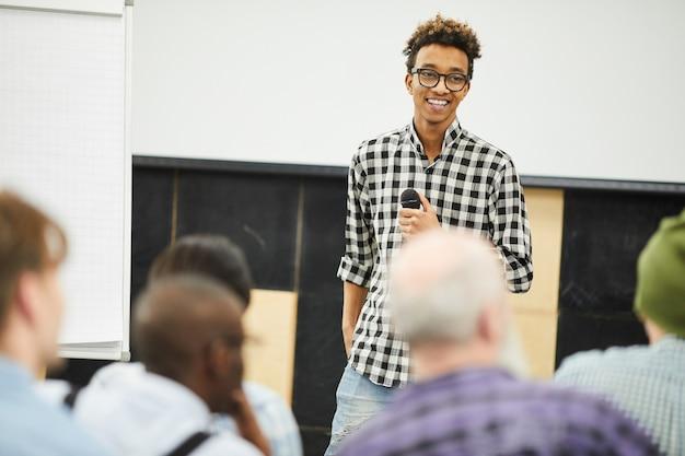 Положительный успешный молодой предприниматель на бизнес-конференции