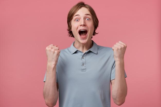 Il giovane studente maschio di successo positivo stringe i pugni nella gioia, come un vincitore, ha ottenuto la vittoria, apre ampiamente la bocca mentre esclama con felicità, ha un'espressione felicissima, isolata su sfondo rosa