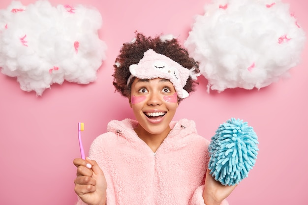 Positive surprised afro american woman concentrated above wears sleepmask and pajama holds toothbrush going to brush teeth applies beauty collagen patches under eyes poses at home