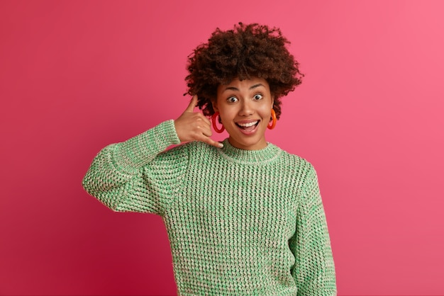 Positive talkative mixed race woman makes call me gesture, keeps contact with friends on self isolation over telephone, smiles pleasantly, poses well dressed indoor, tries to gets someones number