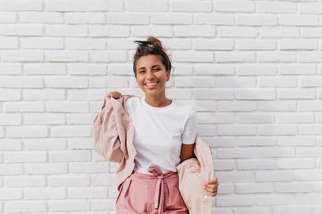 La donna abbronzata positiva in maglietta bianca mette sulla giacca rosa
