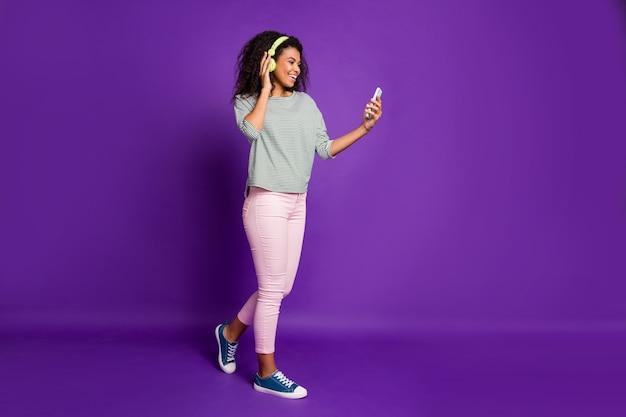 Позитивный подросток афроамериканец пользуется смартфоном просматривает популярные песни