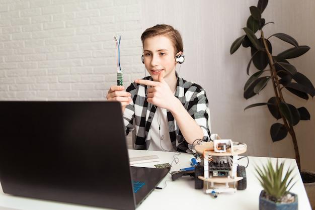 Позитивный ребенок-подросток ведет блог о робототехнике дома во время изоляции от пандемии covid-19. stem-образование, дистанционное обучение, технологическая концепция
