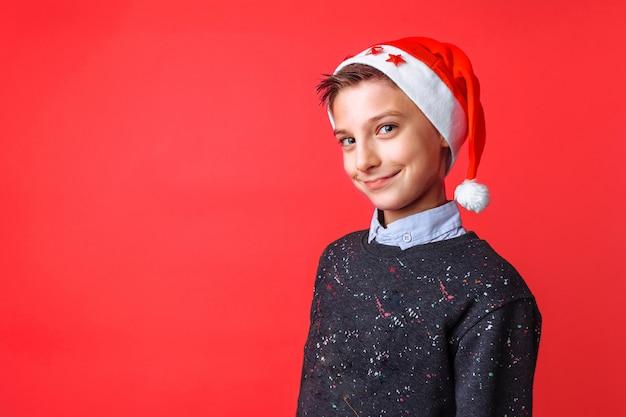 Позитивный подросток в новогодней шапке, парень улыбается на красной стене