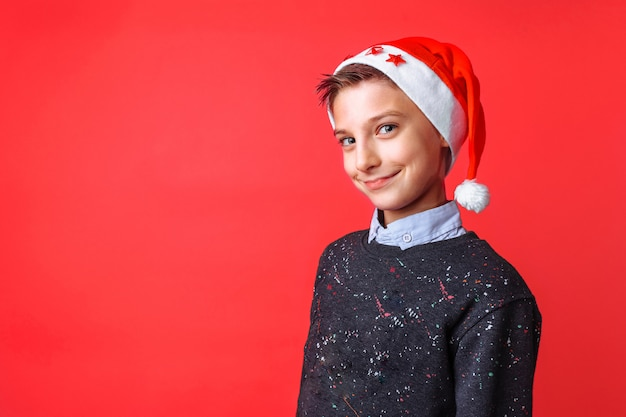 Positive teen in santa hat, guy smiling on red wall