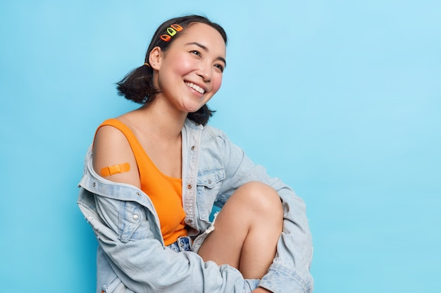 Positive teenage asian girl with two pony tails looks gladfully aside shows plastered shoulder happy after getting vaccination feels protected wears stylish denim jacket isolated on blue wall