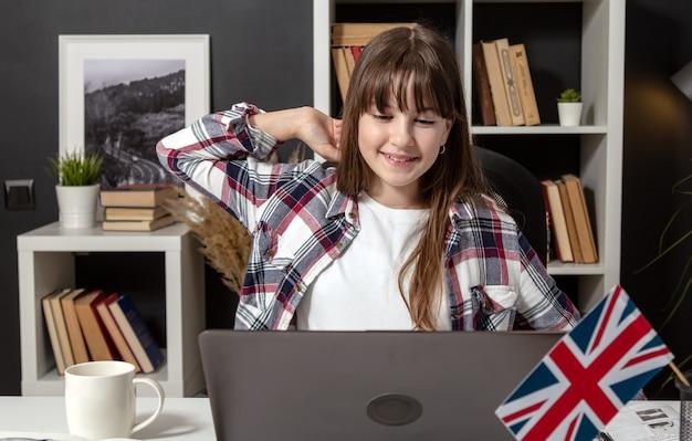部屋の机、正面図に座ってストレッチノートパソコンの画面を見ているポジティブな10代の少女