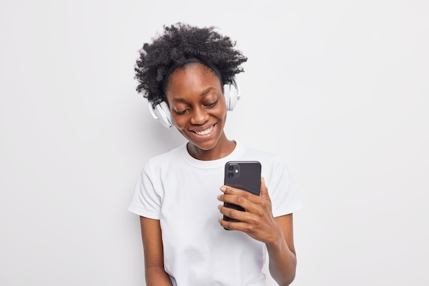 Positive teenage girl with afro hair listens to  favorite song from playlist holds modern smartphone uses wireless headphones