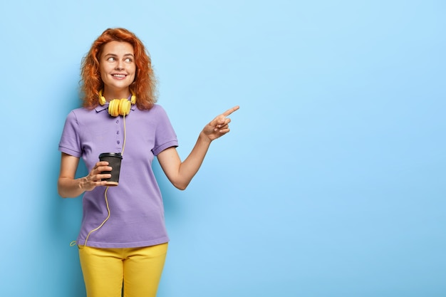 Positive teenage girl with red short hair, points away on free space, holds paper cup of coffee