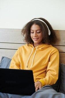 Позитивная девочка-подросток смешанной расы с кудрявыми волосами сидит в постели и слушает музыку во время чата в социальных сетях с помощью ноутбука