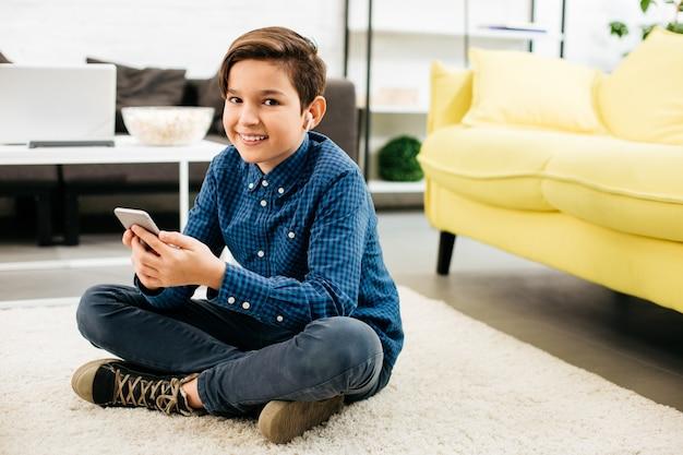 家で柔らかいカーペットの上に座って、現代のスマートフォンを持って、彼の耳にワイヤレスイヤホンを持っている間微笑んでいるポジティブなティーンエイジャー