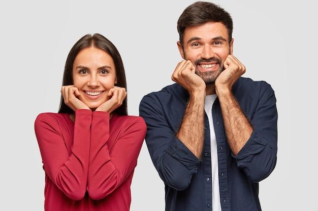 Gli adolescenti positivi tengono le mani sotto il mento, hanno sorrisi caldi a trentadue denti