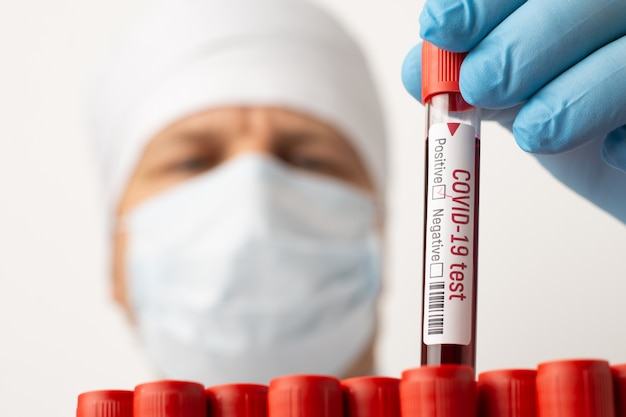 Positive test-tube with blood samples in researcher`s hands. disappointed laboratory worker has found new case of covid-19