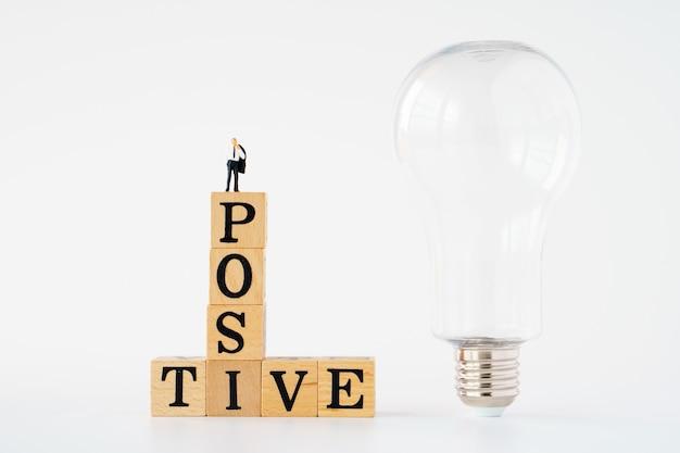 ポジティブシンキングのシンボル。 「ポジティブ」という言葉で木製の立方体のミニチュアビジネスマン。電球。白色の背景。