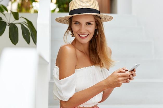 肯定的な思いやりのあるリラックスした女性の夏帽子、ワイヤレスインターネットに接続されている現代の携帯電話でメッセージを入力すると、スタイリッシュな服を着ています。