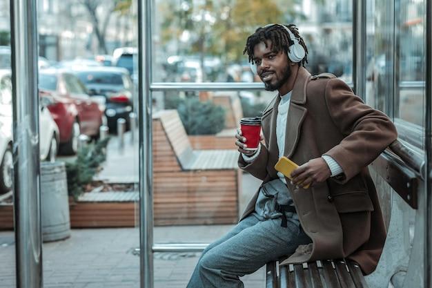 ポジティブな考え。紙コップを持ってバスを探している喜んでひげを生やした男