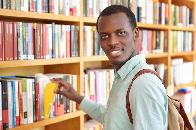 Positive traveler carrying backpack picking book in bookstore