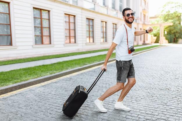 Позитивный путешественник с бородой, с чемоданом и фотоаппаратом, бегущий по улицам в сторону отдыха