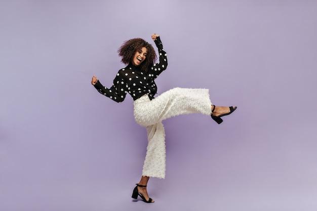 Позитивная модная девушка с классной прической в черной блузке в горошек, необычных брюках и современных каблуках радуется и смотрит вперед