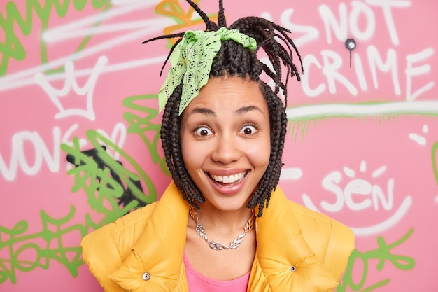 Positive trendy young adult belongs to youth subculture who have common clothes style and behaviour wears yellow vest has surprised happy look at camera poses against graffiti wall