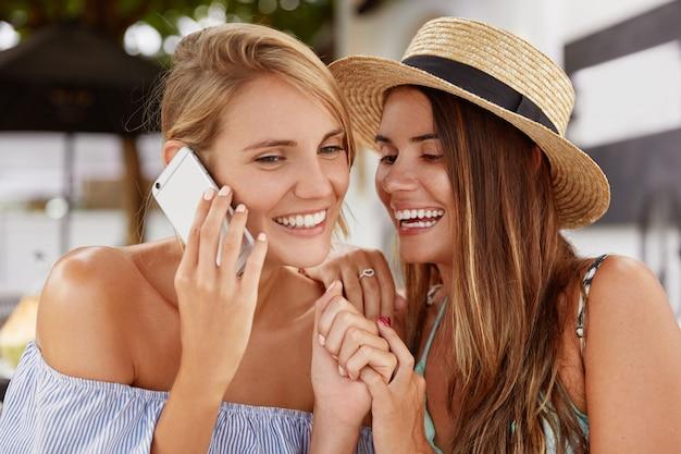 Две позитивные женщины имеют гомосексуальные отношения, сидят рядом и веселятся. милая молодая женщина в соломенной шляпе прерывает свою девушку для мобильного разговора. лесбийская пара