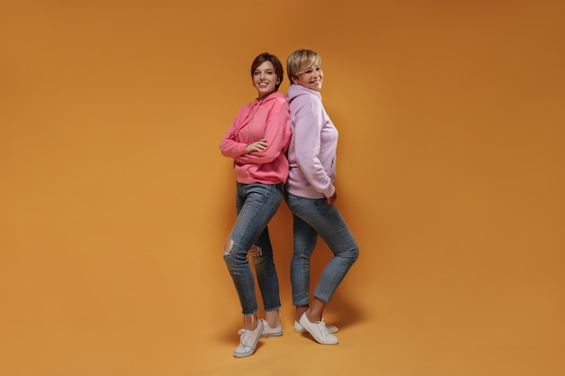 Позитивные две коротковолосые дамы с милыми улыбками в модной розовой толстовке, современных джинсах и крутых кроссовках смотрят в камеру на оранжевом фоне.