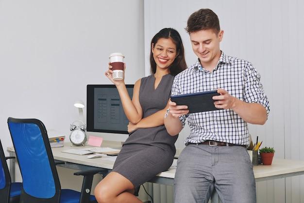 커피 브레이크 동안 태블릿 컴퓨터에서 만든 인터페이스를 테스트하는 긍정적 인 ui 부서 디자이너
