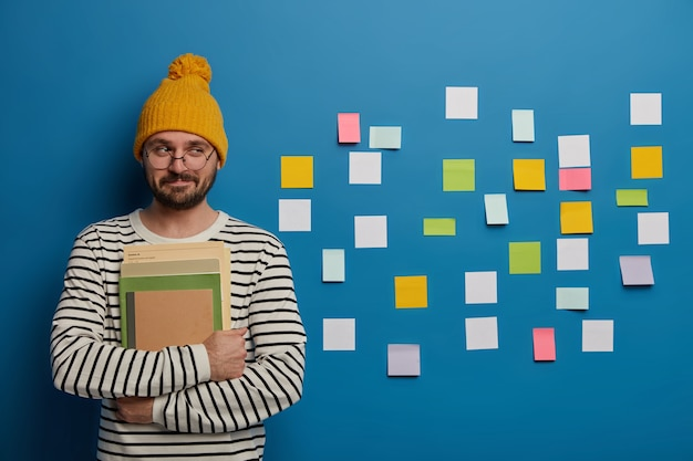 Positive unshaven college student stands near reminder schedule wall with sticky notes, holds notepads and textbooks, enjoys studying and learning something new