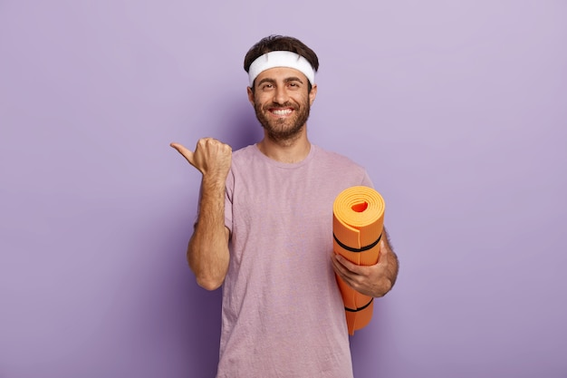 Positive unshaven guy wears white headband and purple t shirt, holds rolled up mat, points aside