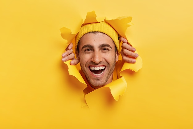Positive unshaven male adult looks happily through yellow paper, shows only face