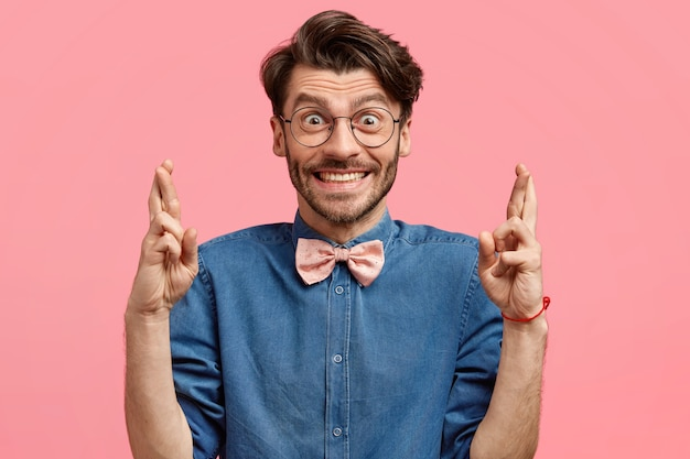 幸せな表情でポジティブな無精ひげを生やした男性は指を交差させ、幸運を願って、ピンクの蝶ネクタイとファッショナブルなデニムシャツを着て、ポジティブな外観を持ち、壁に隔離されています