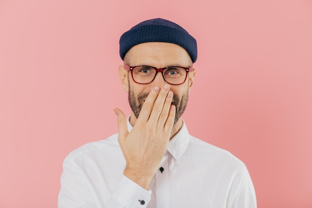 Positive unshaven man covers mouth with palm, giggles positively, wears spectacles
