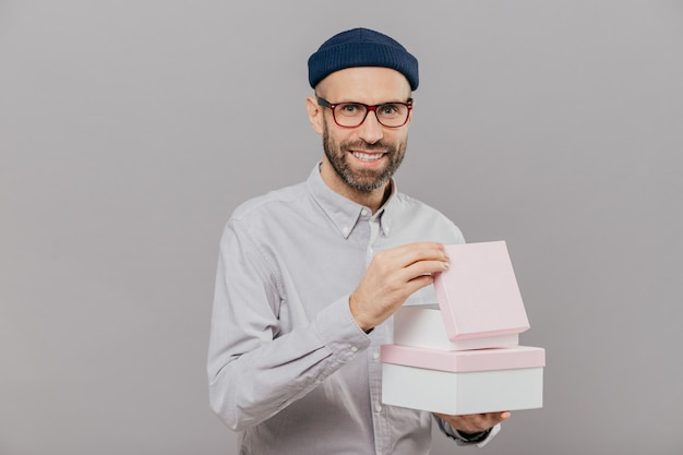 Positive unshaven man has stubble, carries boxes with present, opens one of them