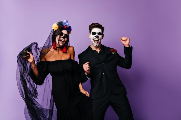 Positive vampires in black clothes dancing together. smiling mexican muerte couple posing on purple background.