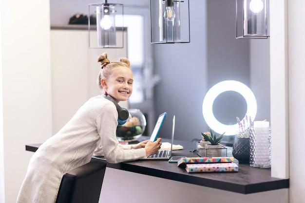 ポジティブな雰囲気。テーブルの近くに立っている間ポジティブな感じの素敵な髪型を持つかわいい青い目の長い髪の女の子