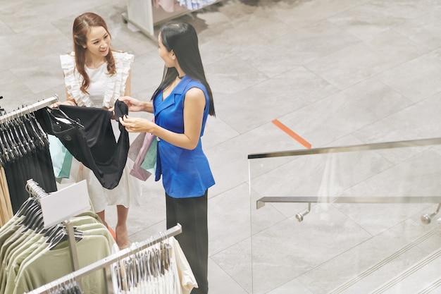 주말을 함께 보낼 때 상점에서 옷을 사는 긍정적 인 베트남 여자 친구