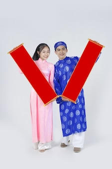 Positive vietnamese young couple in traditional custom for lunar new year as known as tet holiday