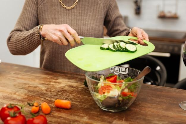 Положительно во время приготовления. трудолюбивая и аккуратная женщина добавляет нарезанные огурцы в стеклянную миску, заканчивая готовить