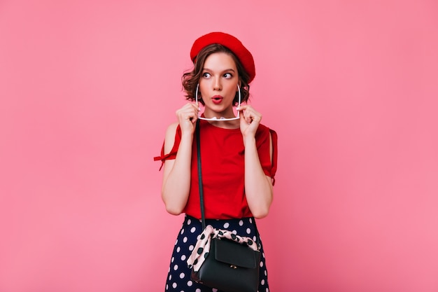 興味を表すかわいい赤いベレー帽のポジティブな白人の女の子。短いヘアカットのdebonairフランスの女性モデルの屋内写真。