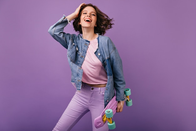 Positive white girl in pink pants posing with skateboard. blithesome curly woman smiling.