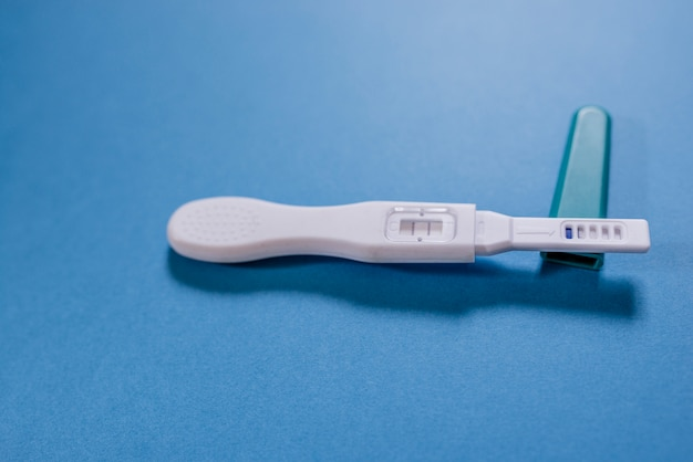 Positive white plastic pregnancy test isolated on blue background.