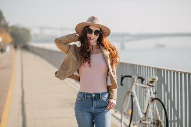 Donna bianca positiva che tocca il suo cappello mentre posa sull'argine