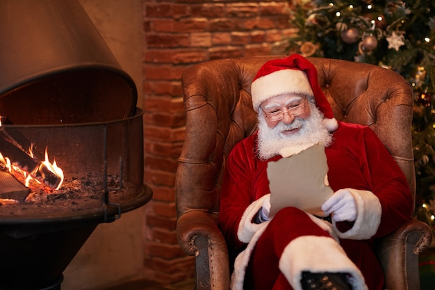 Positive whitebearded santa claus sitting in armchair and reading letter from child at fireplace