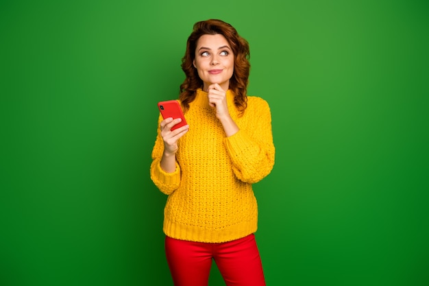 Positive woman addicted social media user use smart phone think thoughts decide what type touch chin look copyspace wear style stylish trendy sweater isolated bright shine color wall