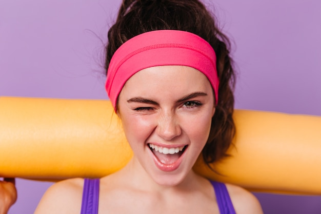 Positive woman athlete in pink headband smiles and winks on purple wall with orange mat for fitness